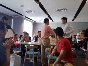 Randy Ng, the manager of the Entrepreneurship Section giving out an appreciation gift to a guest at the Entrepreneurship Students